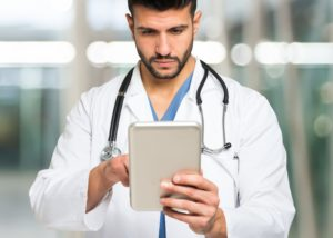 Doctor using his tablet. Large copy-space